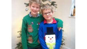 Two young boys wearing Christmas jumpers