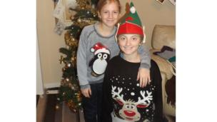 A boy and girl wearing Christmas jumpers by their tree