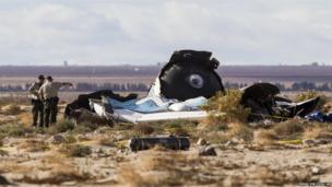 Law enforcement officers take a closer look at the wreckage near the site where a Virgin Galactic space tourism rocket, SpaceShipTwo in Southern California's Mojave Desert,