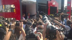 The media surround the Ferrari bus