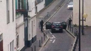 Armed gunmen face police officers near the offices of the French satirical newspaper Charlie Hebdo in Paris on 7 January 2015