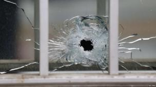 A bullet's impact is seen on a window at the scene after a shooting at the Paris offices of Charlie Hebdo, a satirical newspaper on 7 January , 2015.