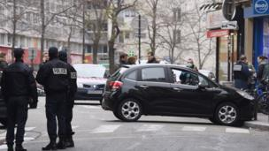 French police officers stand next to the car used by armed gunmen who stormed the Paris offices of satirical newspaper Charlie Hebdo on 7 January 2015