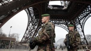 French soldiers patrol in front of the Eiffel Tower on January 7, 2015 in Paris as the capital was placed under the highest alert status