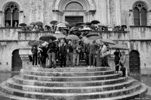 Spectators take shelter under umbrellas