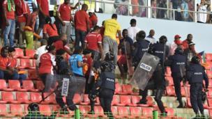 Policemen evacuate a tribune