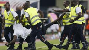 Security detain a fan on the pitch