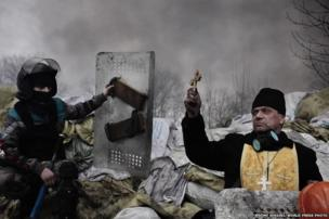 An Orthodox priest blesses protesters on a barricade, 20 February 2014 in Kiev, Ukraine