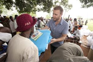Gary Barlow offers a mosquito net to a woman