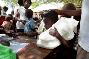 A child is handed a mosquito net