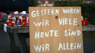 "A poster reading ""Yesterday we were many, today we are alone"" can be seen in front of a memorial of flowers and candles near the Joseph-Koenig-Gymnasium secondary school in Haltern am See, western Germany"
