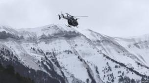 A rescue helicopter from the French Gendarmerie flies over the snow covered French Alps
