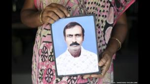 Sabitri Mondal holds picture of her husband