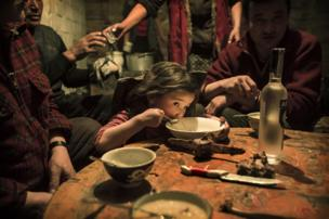 Herder Shohan's family enjoy a last family meal before they separate - copyright Timothy Allen