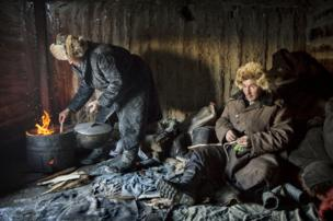 Herders keep warm in a hut on their mountainous migration route - copyright Timothy Allen
