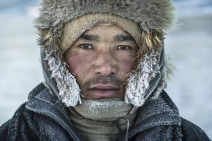 Kazakh nomadic herder Shohan, his frozen breath caught on the fur of his hat - copyright Timothy Allen