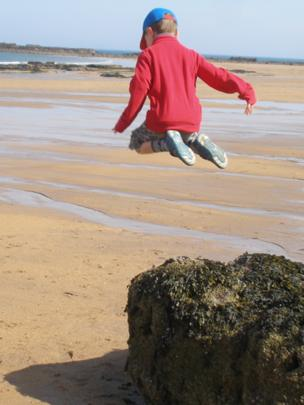 Boy jumping off a rock