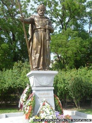 A daytime full-length shot of the statue with floral wreaths around the base