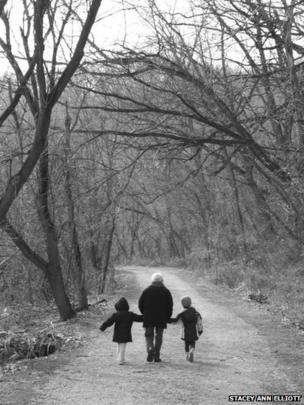 Woman and two children walking in the woods