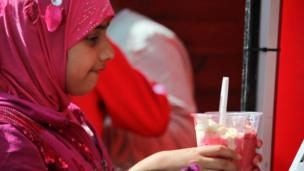 A young girl in pink gets some dessert