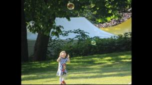A young girl chases bubbles