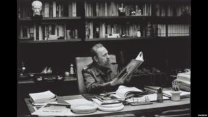 Castro observa fotos da revolução de 1959 em seu escritório em Havana