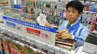 The shop manager of a convenience store updates price tags as Japan's consumption tax raises from five percent to eight percent in Tokyo on 31 March 2014