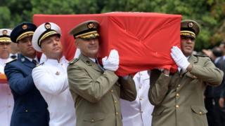 Des officiers militaires portent le cercueil du défunt président Essebsi lors de ses funérailles nationales, au palais présidentiel de Carthage, le 27 juillet 2019.