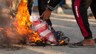 raqis burns the American flag in the southern city of Basra on December 30, 2019