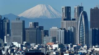 Japan's highest mountain, Mount Fuji (C) is seen behind the skyline of the Shinjuku area of Tokyo on December 6, 2014.