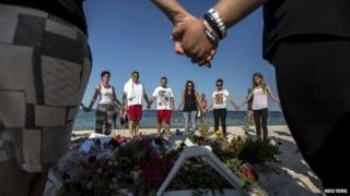 People hold hands as they pray in a circle around bouquets of flowers laid as mementos on the beach of the Imperial Marhaba resort