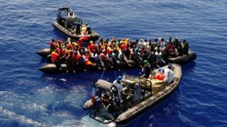 Small boats are pictured attending to migrants on top of an inflatable boat they are loaded on to.