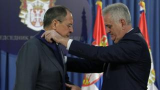 Russian foreign minister Sergei Lavrov (L) receives a medal from Serbian President Tomislav Nikolic (12 Dec)