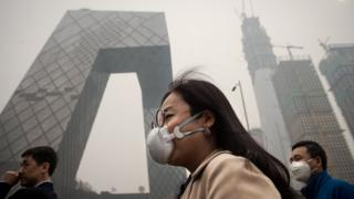 A man and a woman wear pollution masks in Beijing