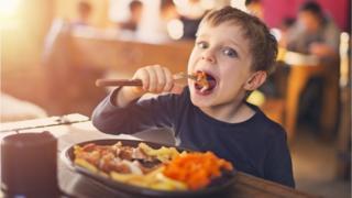 Niño comiendo carne.