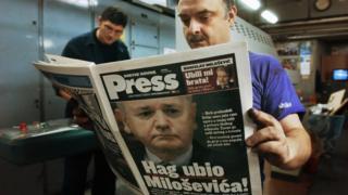 Работник белградской типографии читает номер газеты, сообщающей о смерти Милошевича в тюрьме