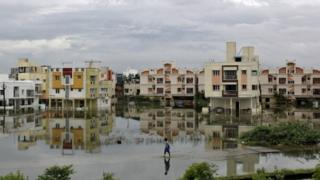 A man walks through a flooded residential area in Chennai, India, December 2, 2015