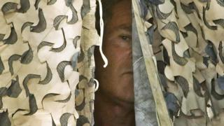 US President George W Bush waits behind a camouflage curtain before being announced to speak to troops at Al-Asad Air Base in Iraq's western al-Anbar province on 3 September 2007