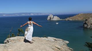 一名女游客在贝加尔湖畔拍照