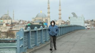 A solitary man walks wearing a face mask