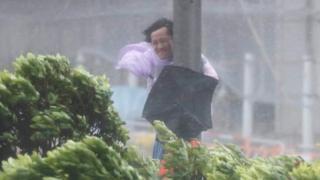 Un hombre en medio de una tormenta en Hong Kong