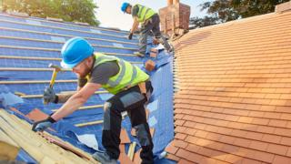 Workers tiling a roof