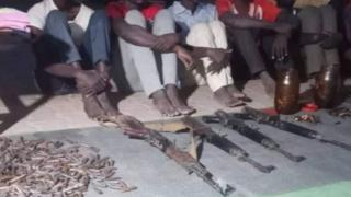 Detainees from Darfur seated next to weapons and bullets