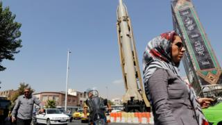 Technology A woman walks past a Shahab-3 ballistic missile and launcher on a street in Tehran, Iran, during Defence Week (26 September 2019)