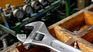 A wrench lies on a workbench at manufacturing firm