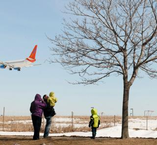 A family watch a plane land at an airport