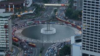 Dòng xe cộ lưu thông qua các tòa nhà cao tầng ở trung tâm Jakarta