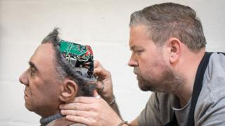 Prosthetic expert Mike Humphrey is considering Fred, a Mesmer robot built by engineering in Cornwall, England.