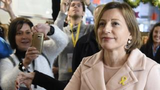 Carme Forcadell looks up and into the distance as bystanders photograph her - her right arm is extended, out of frame, towards the ballot box, and on her lapel she wears the yellow ribbon adopted as a symbol of solidarity with other jailed leaders