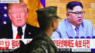A South Korean soldier walks past a TV screen showing pictures of US President Donald Trump and North Korean leader Kim Jong Un at a railway station in Seoul